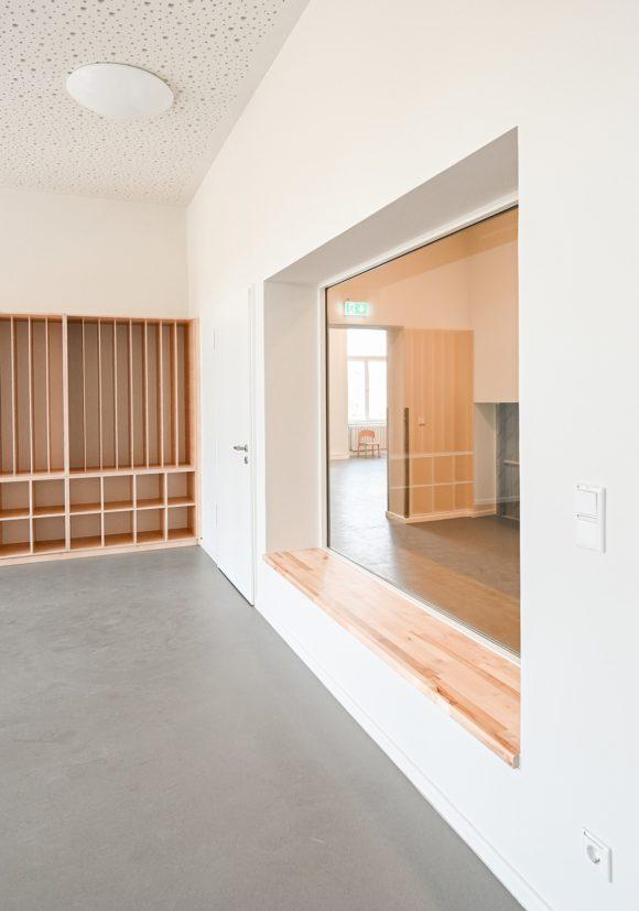 Garderobenbereich mit Sichtfenster in die Kita des Projektes Kindergarten Wirbelwind in Berlin.
