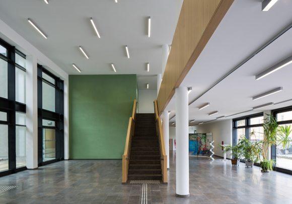 zweigeschossiger Luftraum mit hölzerner Freitreppe und grünen Farbakzenten des Neubaus der zwei Landesministerien in Potsdam.