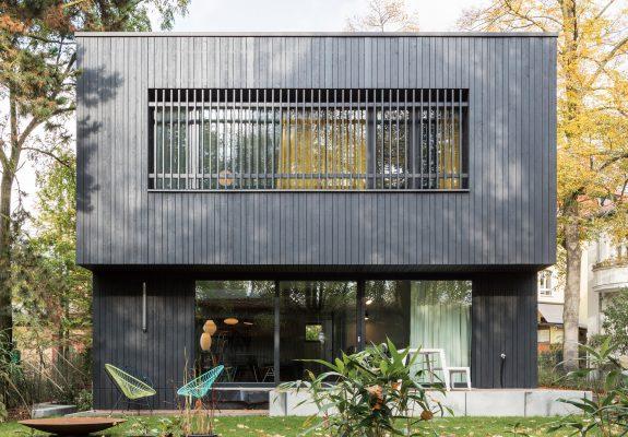 Vorgarten mit Pool und großer Terrasse des in schwarzem Holz verkleideten Einfamilienhauses A28 in Berlin.