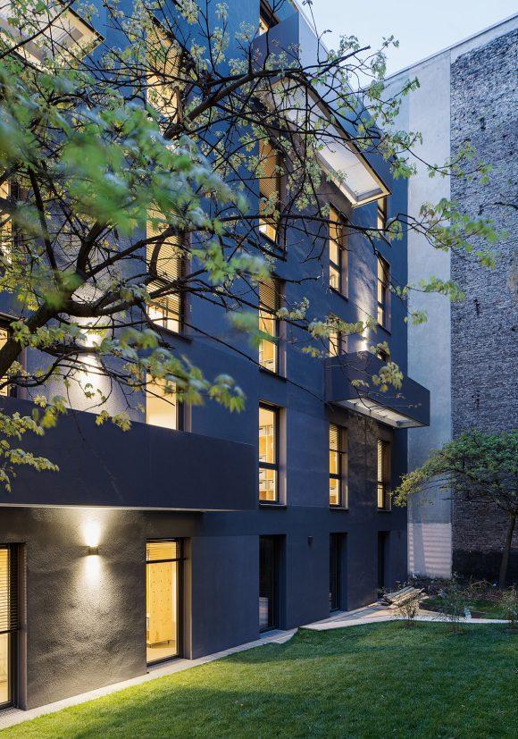 Nachtansicht der Hoffassade des in Holzmodulbauweise errichteten Wohnhauses Stromstraße in Berlin.