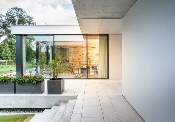 Terrasse mit Vordach und Treppe zum Pool des Einfamilienhauses in Wassernähe in Brandenburg.
