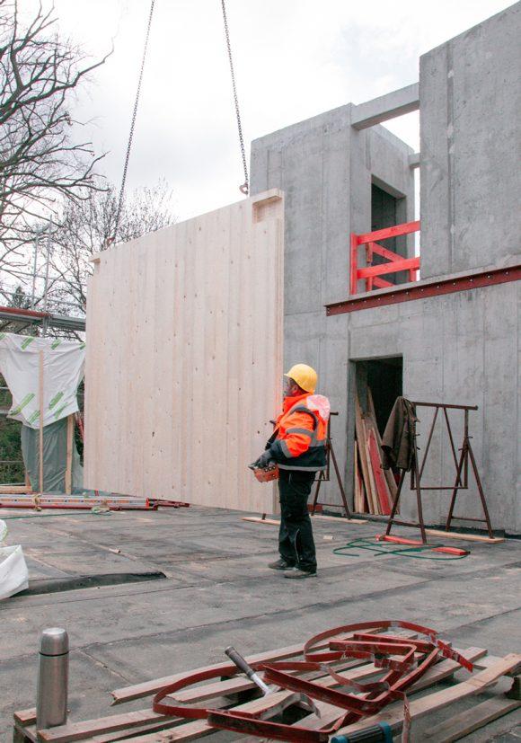 Bauarbeiter montiert Holzwände auf der Baustelle des Wohnhauses in Berlin Zehlendorf.