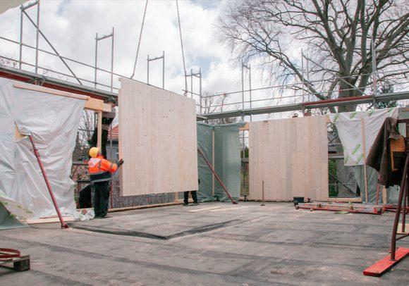 Bauarbeiter montieren Holzwände auf der Baustelle des Wohnhauses in Berlin Zehlendorf.