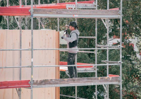 Bauarbeiter auf dem Gerüst auf der Baustelle des Wohnhauses in Berlin Zehlendorf.