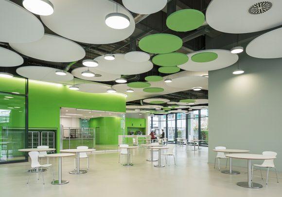 Cafeteria mit grünen Wänden, einer Glastrennwand, runden Deckenelementen und Tischgruppen des IZS, Stuttgart.