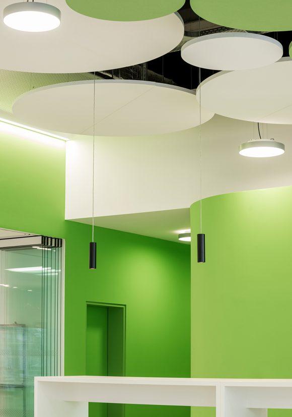 Detail mit grüner und weißer Wand und runden Deckenelementen im Cafeteria des IZS, Stuttgart.