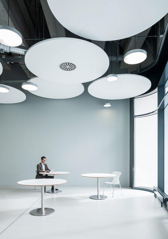 Ecke mit grauer Wand, runden Tischen und Deckenelementen im Cafeteria des IZS, Stuttgart.