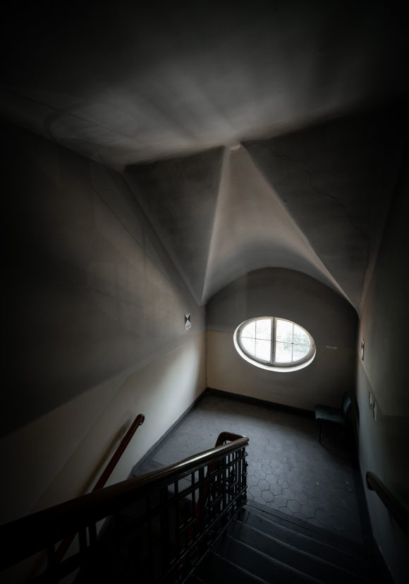 Treppenhaus mit rundem Fenster in der Kurt-Tucholsky-Grundschule in Berlin.