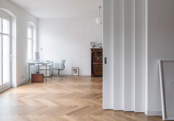 Wohnraum mit Teleskop Schiebetür der umgebauten Altbauwohnung in Berlin Mitte.