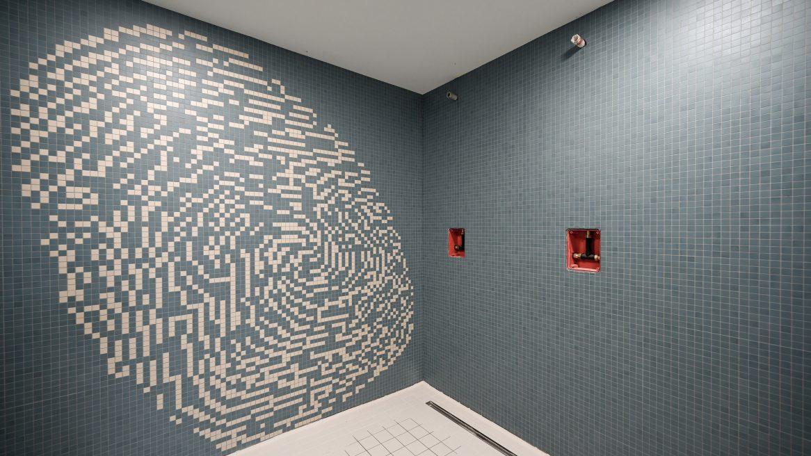 Duschbereich mit blauen Fliesen mit eingelegtem weißen Fingerabdruck des Polizeireviers Werdau.