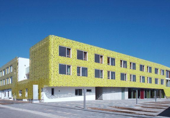 Vorplatz mit großzügigem Eingang und grüner Lochblechfassade mit Blattmuster des Gesundheitszentrums Seekirchen.