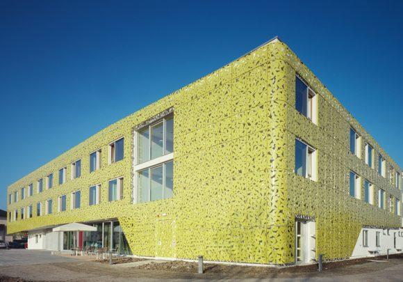 grüner Lochblechfassade mit Blattmuster des Gesundheitszentrums Seekirchen.