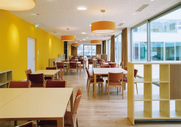 Gemeinschaftsbereich mit gemütlichen Tischgruppen und großzügiger Glasfassade des Gesundheitszentrums Seekirchen.