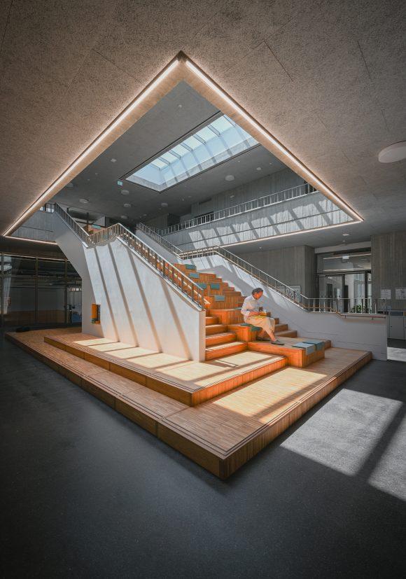 Xaver Egger von Sehw Architektu sitzt auf der zentralen Treppe in der Grundschule am Jungfernsee am Tag der Architektur 2021.