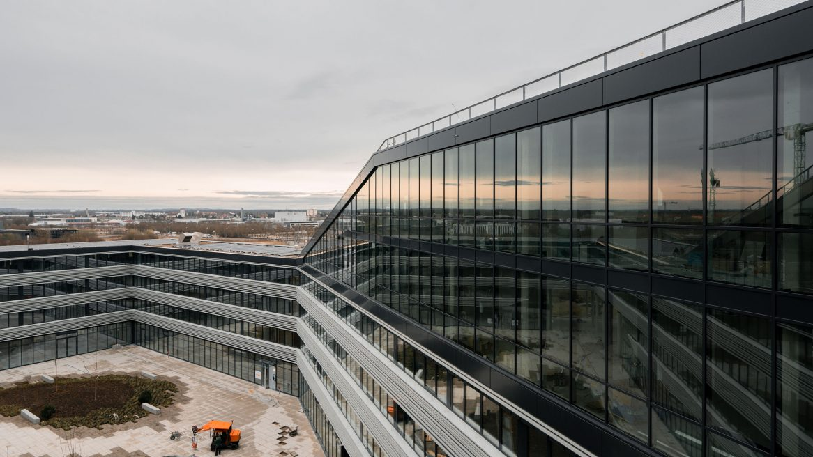 Blick vom Obergeschoss nach Innenhof und die Spiegelung des Sonnenuntergangs auf der Fassade des Verwaltungsgebäudes für die Leitwerk GmbH in Augsburg.