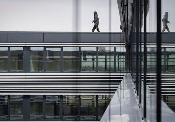 Blick vom Obegeschoss auf die Fassade und den laufenden Mann auf dem Dach des Verwaltungsgebäudes für die Leitwerk GmbH in Augsburg.
