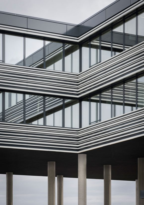 Blick vom Innenhof auf die Fassade und großen Stützen des Verwaltungsgebäudes für die Leitwerk GmbH in Augsburg.